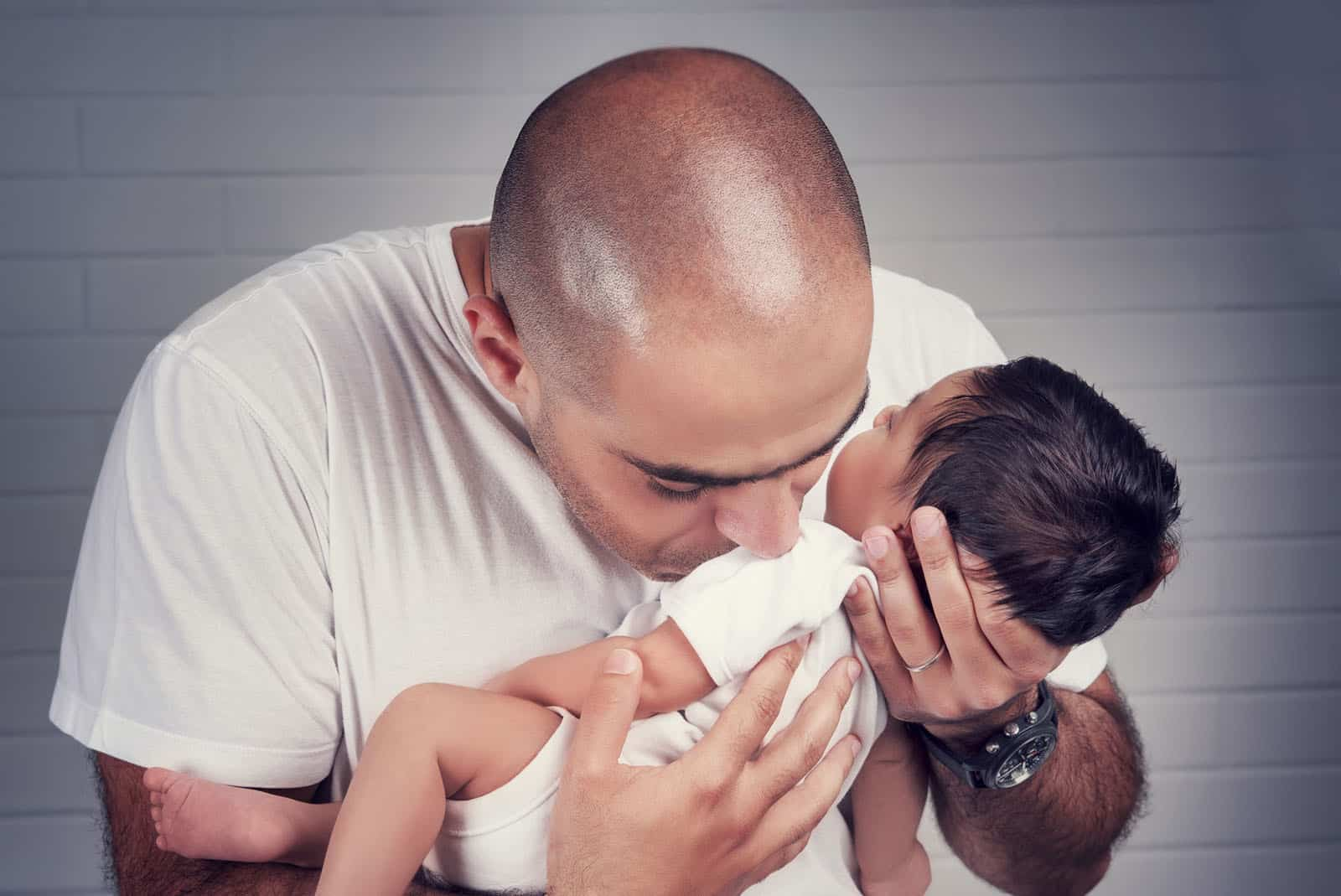 StandUpGirl dad kisses newborn baby