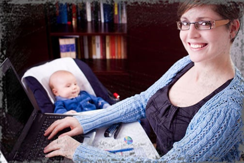 StandUpGirl mother on computer with baby next to her