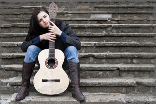 StandUpGirl girl sits on steps holding guitar