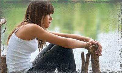StandUpGirl woman sits by water