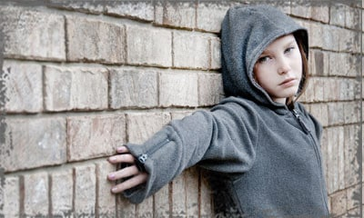 StandUpGirl girl with hood stands against wall