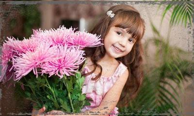 StandUpGirl little girl looks from behind flowers